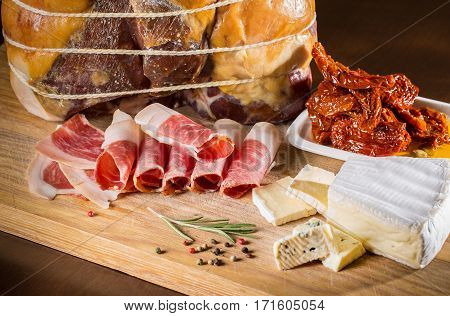 Slices of ham. Slices of meat. Different kinds of meat on wooden background with spices and seasonings. Thin slices of ham on white background. Ham and herbs on black stone slate board. Ham.