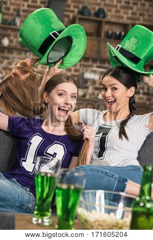 excited young women in green hats celebrating st patricks day