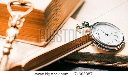 Vintage paper knife and pocket watch on the bookshelf with stack of open books in bright light