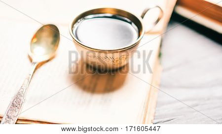 Coffee cup and spoon on the bookshelf with stack of open books in bright sun. Selective focus