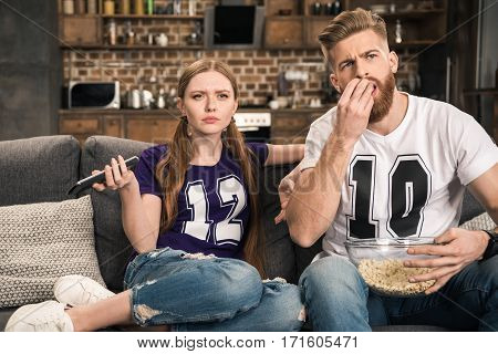 portrait of concentrated couple watching movie with popcorn at home