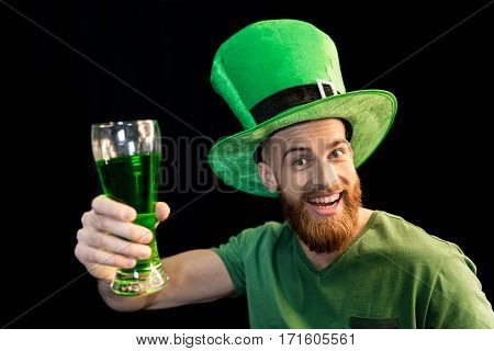 portrait of excited man holding glass of beer on St.Patrick's day on black