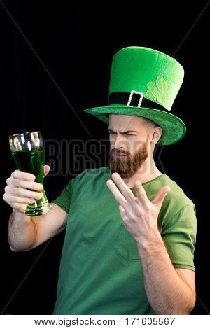 Portrait of upset man holding glass of beer on St.Patrick's day on black
