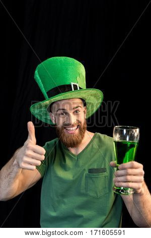 portrait of cheerful man holding glass of beer on St.Patrick's day and showing thumb up on black