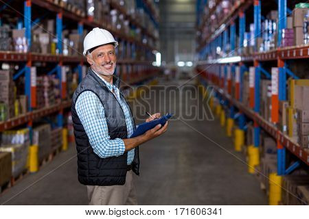 Portrait of warehouse worker checking the inventory in the warehouse