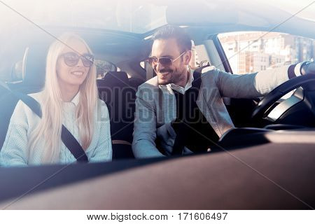 A young woman and a young man are laughing in the carenjoying in the road trip.The man is driving.