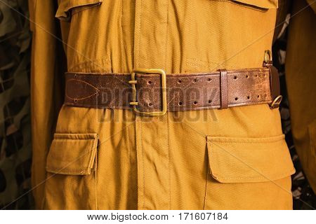 Russian vintage yellow military uniform with a belt the Second World War on the background of a camouflage net.