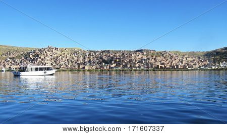 a distant tourist boat moving across Lake Titicaca