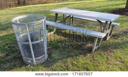 A metal trash can next to an empty picnic table at a park