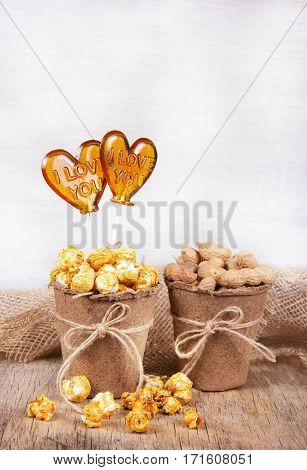 Paper bucket of caramel popcorn and peanuts. Two lollipop in the shape of a heart. Set to view the movie. Copy space.