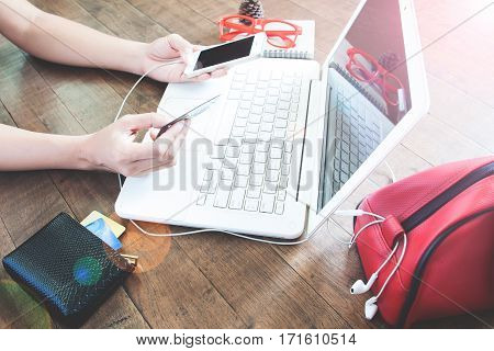 Woman hand holding credit card and using mobile device and laptop Online shopping concept