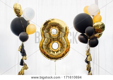 Decoration for 8 years birthday, anniversary, celebration of the thirtieth anniversary, white background, gold and black balloons with tassels