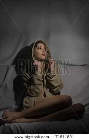 Young blond woman with hood on couch