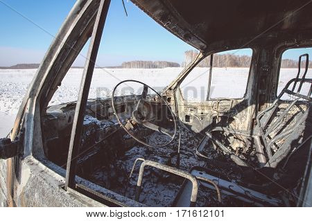 Lonely burnt car in the cold winter