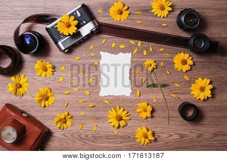 White long sheet of paper lying on the wooden table. Vintage camera lenses and photographic film unfolded on a retro background. Designer composition with flowers. Case for camera. Space for text.