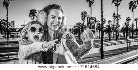 Mother And Daughter Tourists Taking Photo With Digital Camera