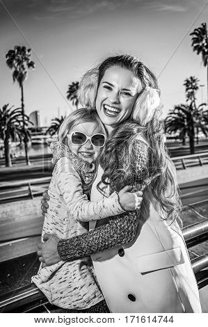 Happy Mother And Child Travellers In Barcelona, Spain Embracing