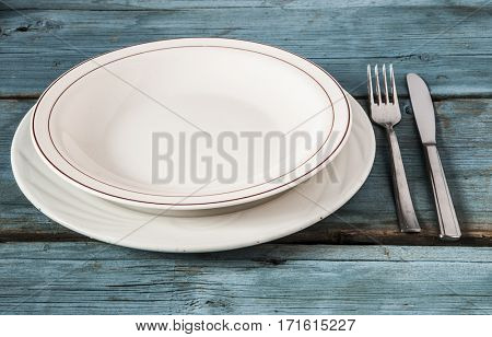 Empty plate with knife and fork on wooden background