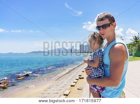Dad And Daughter Playing On The Promenade By The Sea. Young Man, Little Girl
