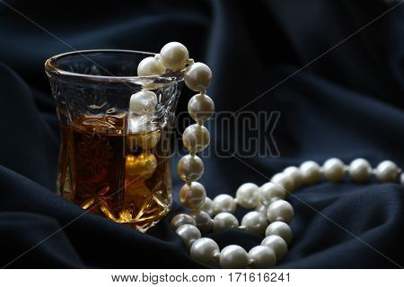 crystal glass with brandy and pearls on black fabric , elegant drink