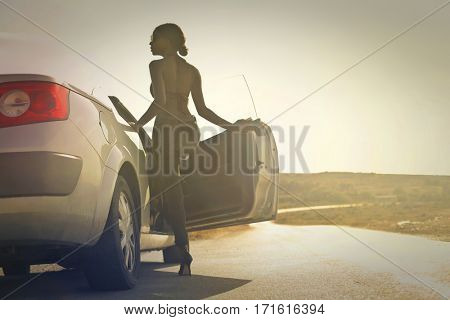 Beautiful black girl getting in her car in the middle of the desert