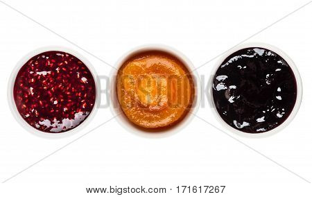Row Of Bowls With Raspberry, Peach, Blueberry Jam On White