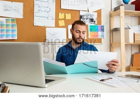 Young successful businessman looking through papers, sitting at workplace with laptop