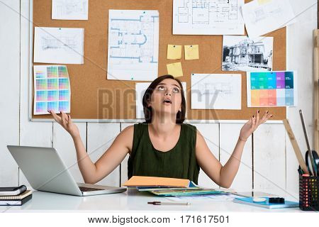 Upset young beautiful businesswoman gesturing, sitting at workplace in office.