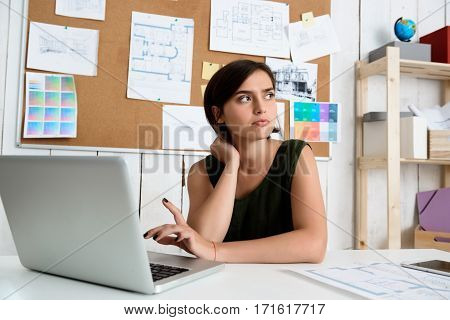 Young beautiful businesswoman thinking, sitting at workplace with laptop.