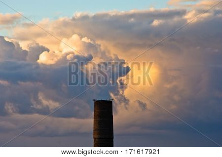 Top of industrial chimney against colorful and picturesque golden clouds at sunset