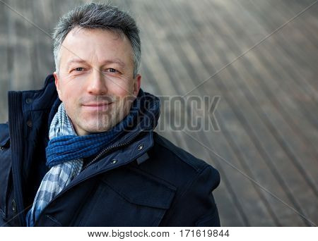 Handsome man. Outdoor winter european male portrait. Attractive confident middle-aged man, city portrait, image toned and noise added.
