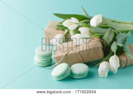 Compliment gift with spring white tulips and macaroons
