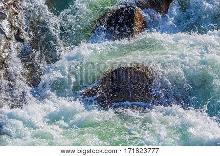 Raging water breaker among rocks of mountain river in winter