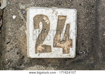the digits with concrete on the sidewalk 24