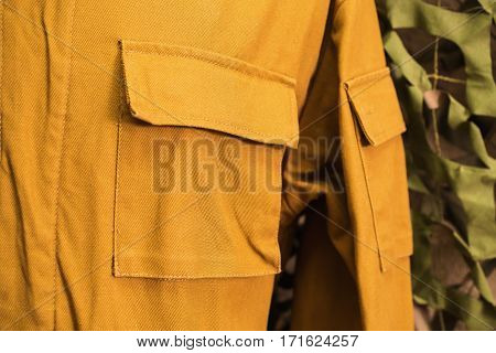 Russian military vintage yellow form the Second World War against the background of a camouflage net. Pocket jacket closeup. Men's style.