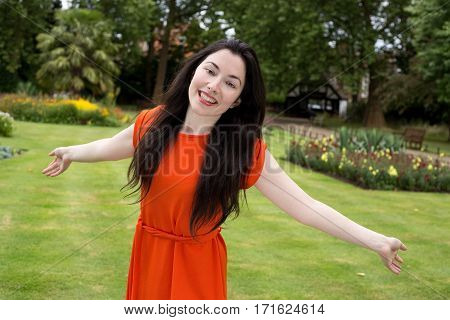 happy girl in the park with outstretched arms.