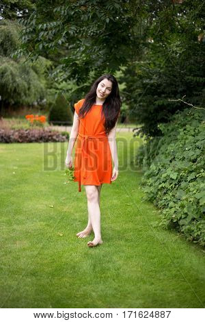 young woman walking on the grass barefoot