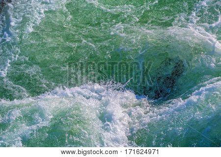 Raging water whirpool among rocks of mountain river in winter