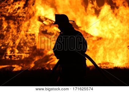 silhouette of firefighter against raging house fire