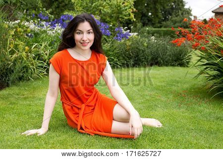 young oman sitting in the park between the flowers