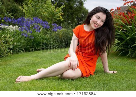 young woman sitting on the grass between the summer flowers
