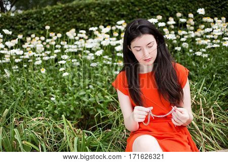 young woman sitting in the park holding some jewellery