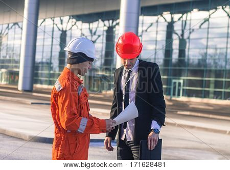 young boss and worker in conversation discussing a construction project. They wear safety helmets. Tablet in hand. Business modern background