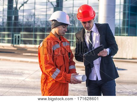 young boss Scold Employee in conversation discussing a construction project on tablet. They wear safety helmets. Business modern background