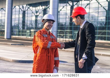 young boss and worker in conversation shaking hands. They wear safety helmets. Business modern background