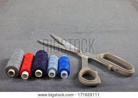 Scissors with thread on grey fabric background