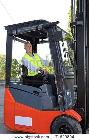 Bald Driver With Safety Vest in Forklift Cabin