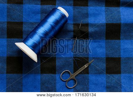 Blue threat with scissors and needle on a colorful fabric