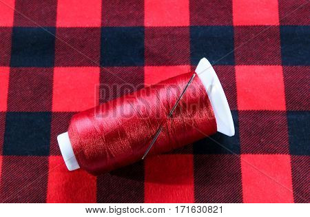 Red threat with needle on red fabric