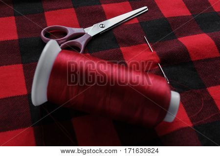 Scissors and needle on a red fabric